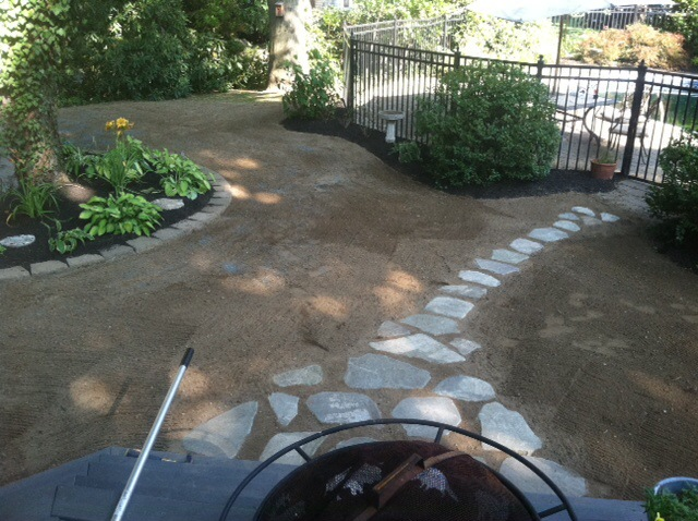 Landscaping process with a fire pit and stone walkway